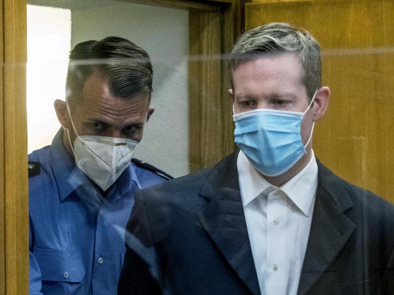 Der Angeklagte (r) wird am ersten Tag des Prozesses mit Mundschutz in einen Gerichtssaal des Oberlandesgerichts gebracht. Foto: Thomas Lohnes/Getty Images Europe/Pool/dpa