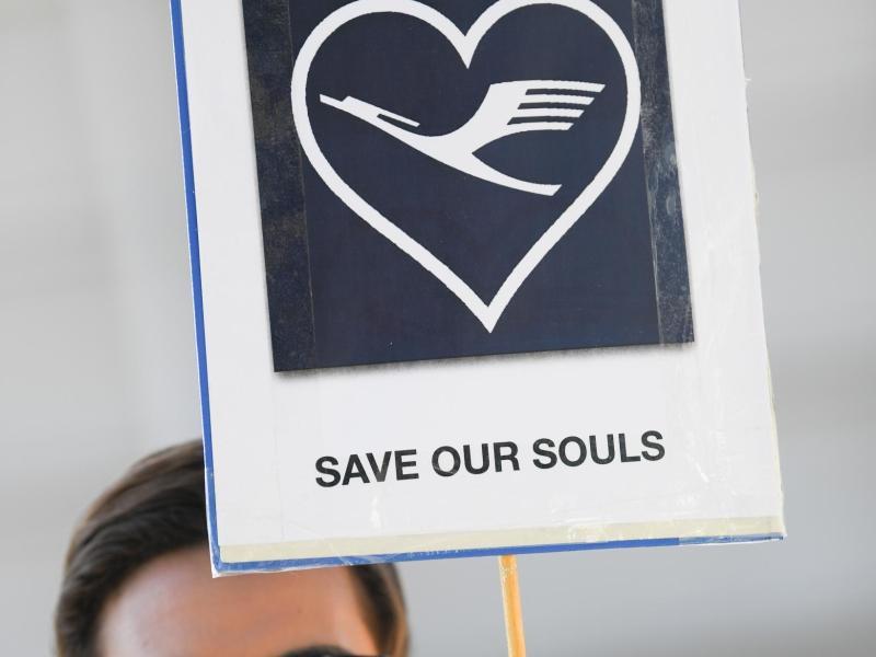 SOS: Ein Lufthansa-Flugbegleiter trägt ein Plakat mit der Aufschrift «Save our souls». Foto: Arne Dedert/dpa