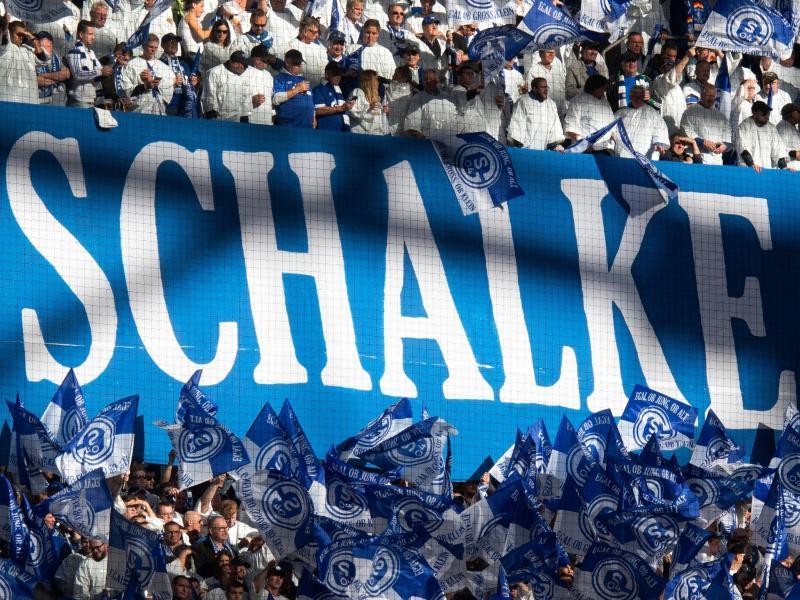 Der finanziell angeschlagene Bundesligaverein soll eine Bürgschaft erhalten - Schalke-Fans schwenken Fahnen. Foto: Bernd Thissen/dpa