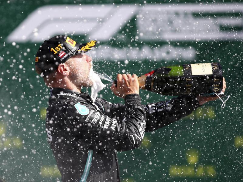 Nach seinem Sieg gönnte sich Bottas einen Champagner-Schluck. Foto: Mark Thompson/pool Getty/AP/dpa