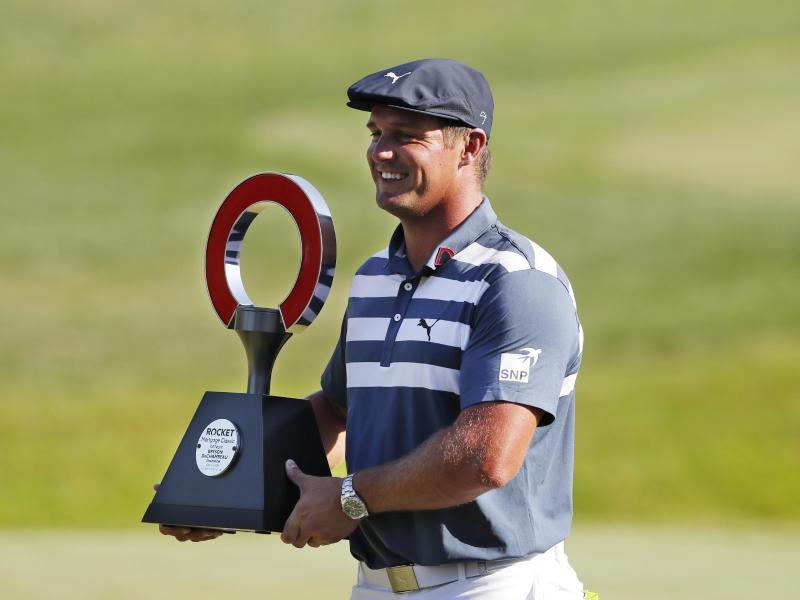 Bryson DeChambeau hält die Trophäe des Golfturniers Rocket Mortgage Classic in den Händen. Foto: Carlos Osorio/AP/dpa