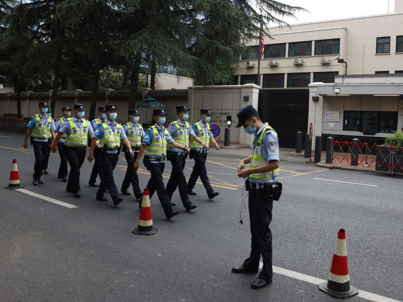 Chinesische Polizisten marschieren am US-Konsulat in Chengdu vorbei. Foto: Ng Han Guan/AP/dpa