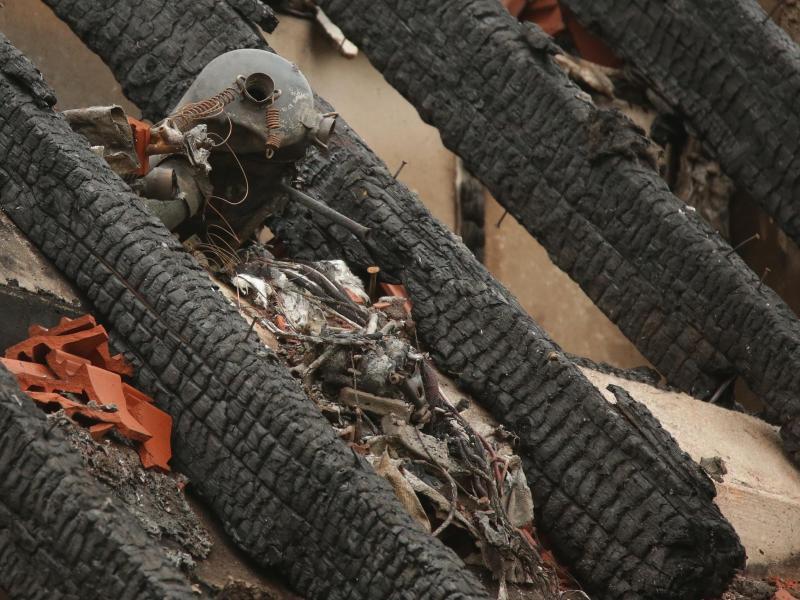 Überreste eines Motors liegen zwischen den verkohlten Dachbalken. Foto: David Young/dpa