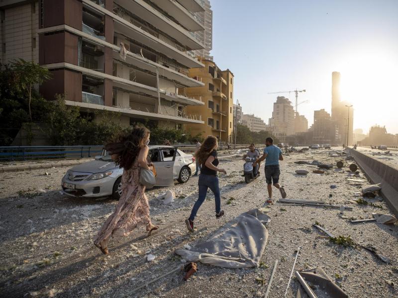 Menschen laufen nach der Explosion über eine von Trümmern übersäte Straße. Foto: Hassan Ammar/AP/dpa