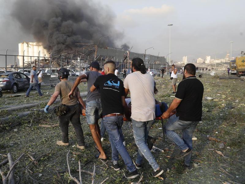 Helfer tragen ein Opfer weg, während im Hintergrund Rauch aufsteigt. Foto: Hussein Malla/AP/dpa