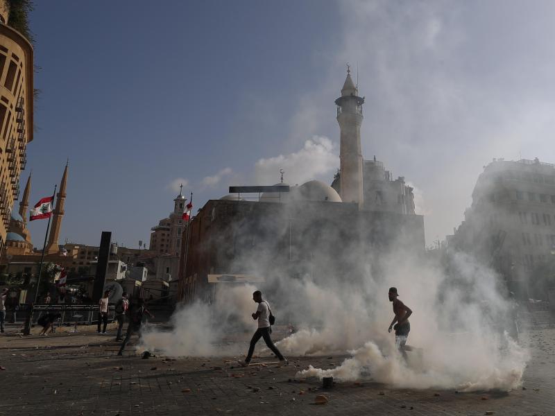 Demonstranten laufen auf dem Märtyrer-Platz durch Tränengas. Foto: Hassan Ammar/AP/dpa