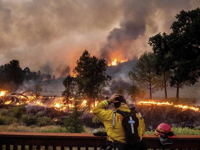 Ein Feuerwehrmann schaut auf das Feuer vor sich. Kalifornien kämpft um die Eindämmung riesiger Waldbrände und hat nun auch Hilfe aus dem In- und Ausland angefordert. Foto: Noah Berger/FR34727 AP/dpa