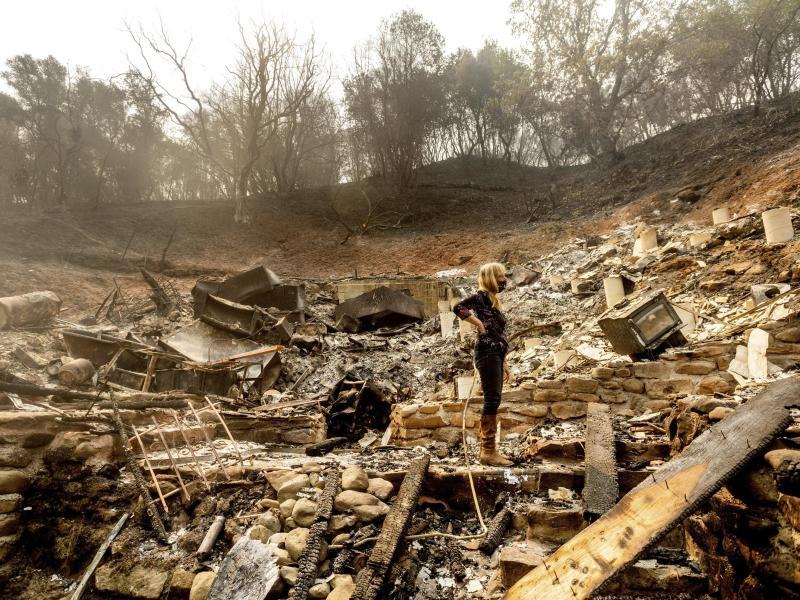 Völlige Zerstörung:Eine Frau inspiziert die Überreste des Hauses ihres Partners in Vacaville. Foto: Noah Berger/AP/dpa