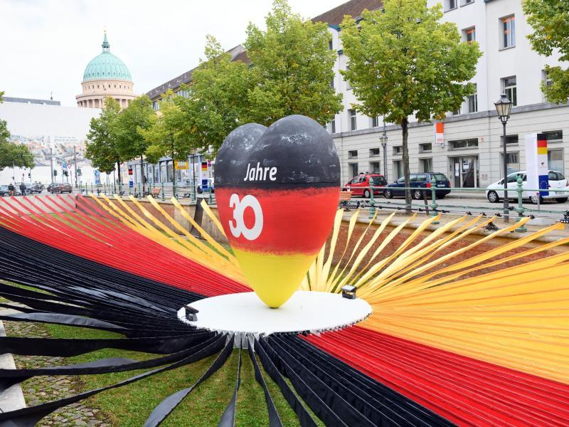 Ein schwarz-rot-goldenes Herz steht während des Eröffnungstages der «EinheitsExpo» in Brandenburgs Landeshauptstadt. Foto: Soeren Stache/dpa-Zentralbild/dpa