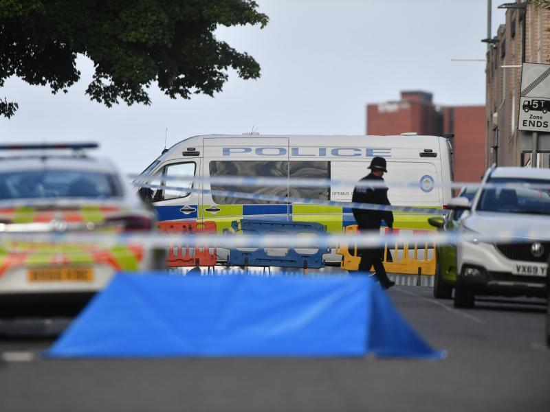Ein Polizist und Fahrzeuge der Polizei stehen an einer Absperrung in der Irving Street in Birmingham. Foto: Jacob King/PA Wire/dpa
