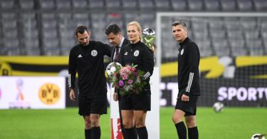 Die scheidende Schiedsrichterin Bibiana Steinhaus wurde vor dem Anpfiff von DFL-Boss Christian Seifert (2.v.l) mit Blumen bedacht. Foto: Sven Hoppe/dpa-Pool/dpa