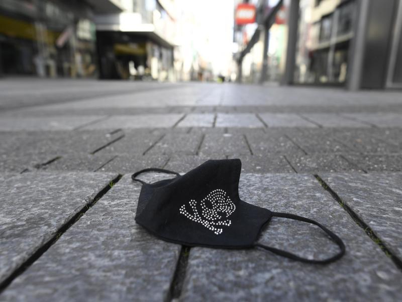 Ein verlorener Mundschutz liegt auf einer Einkaufsstraße. Foto: Roberto Pfeil/dpa/Symbolbild/Archiv