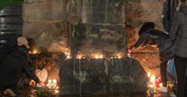 Menschen zünden an der Porta Nigra inTrier Kerzen für die Opfer der Amokfahrt an. Foto: Harald Tittel/dpa