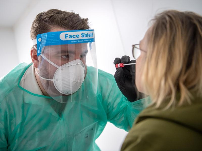 Ein Abstrich für einen PCR-Test wird von einem Mitarbeiter im Corona-Testzentrum genommen. Foto: Sina Schuldt/dpa