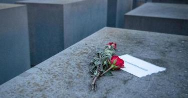 Rosen liegen mit einem Zettel mit der Aufschrift '#weremember' am Holocaust-Mahnmal in Berlin. Foto: Dorothee Barth/dpa