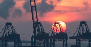 Sonnenuntergang hinter den Containerbrücken des HHLA Containerterminal Tollerort in Hamburg. Die Corona-Krise reißt tiefe Löcher in den Staatshaushalt. Foto: picture alliance / Christian Charisius/dpa