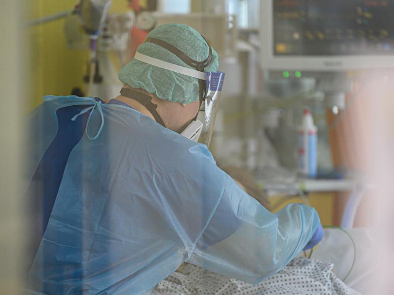 Ein Intensivpfleger ist auf der Covid-19 Intensivstation mit der Versorgung von Corona-Patienten beschäftigt. Foto: Robert Michael/dpa-Zentralbild/dpa
