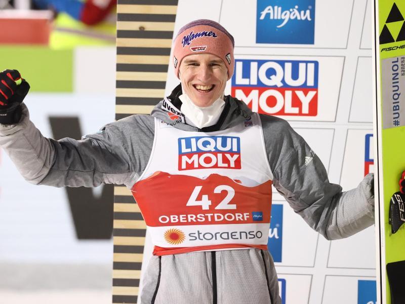 Karl Geiger jubelt auf dem Podium über den zweiten Platz. Foto: Daniel Karmann/dpa