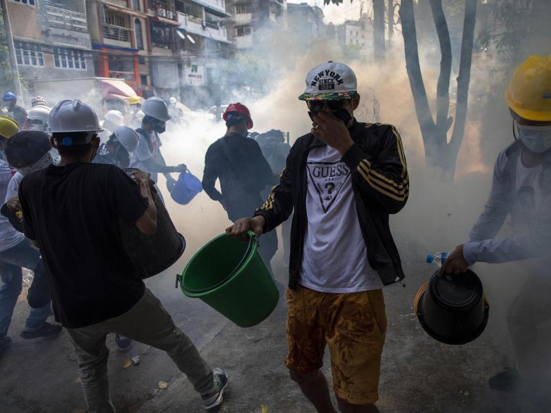 Demonstranten mit Helmen und Mund-Nasen-Schutz versuchen, rauchende Tränengaskanister mit Wasser zu löschen. Foto: Thuya Zaw/ZUMA Wire/dpa