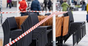 Die Tische und Stühle eines Cafes sind mit Flatterband abgesperrt. Foto: Sven Hoppe/dpa
