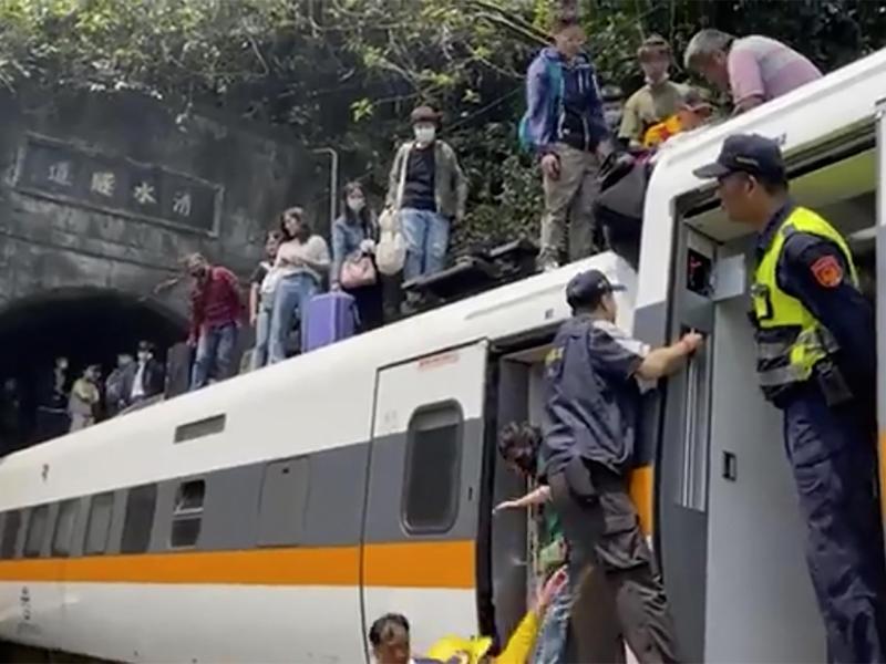 Passagieren wird geholfen, aus dem entgleisten Zug zu klettern. Foto: Uncredited/hsnews.com.tw/AP/dpa
