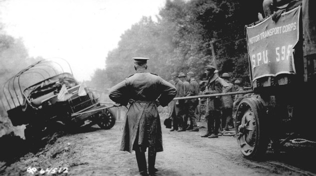 During the 1919 transcontinental convoy, west of Grand Island, Nebraska, soldiers use a winch to pull a Class B truck out of a ditch. Lt. Col. P. V. Kieffer surveys the scene. (Eisenhower Library)