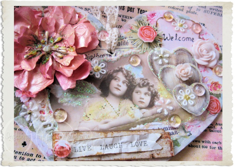 Details of handmade mixed media vintage style heart with pink flowers
