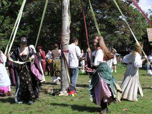 Personas bailando el Maypole Dance con lazos