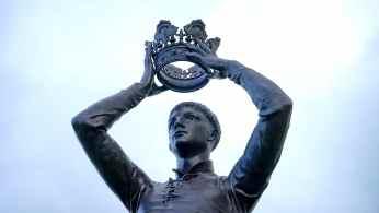 Estatua de Rey levantando la corona