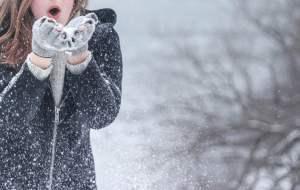 Mujer soplando en la nieve