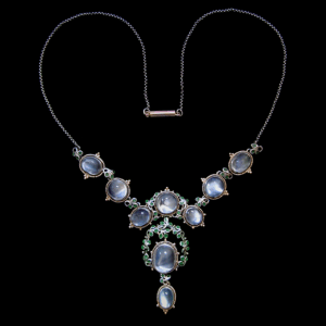 Jessie M King for Liberty & Co. A silver and gold necklace set with moonstones within borders of blue/green enamelled leaves surrounded by gold wire wirework and gold florets. The silver chain with a gold clasp. British. Circa 1900. Size: Height of drop pendant only 4.4 cm. Width 2 cm. Width across three moonstones 11 cm. Total length around necklace 41 cm. Sold by Van den Bosch.