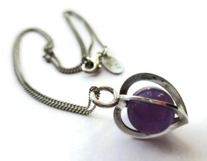 Caged amethyst bead ina heart-shaped sterling silver cage, by Elis Kauppi for Kupittaan Kulta.