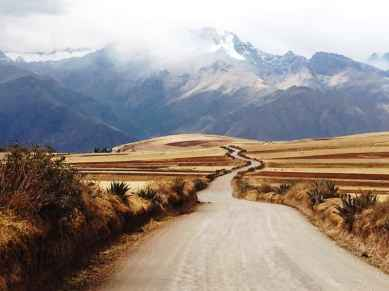 Strada che attraversa territorio arido arrivando alle montagne