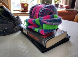 A ball of yarn and half-knit brightly-coloured sock resting atop a Kobo and a copy of Ray Bradbury's Something Wicket This Way Comes.