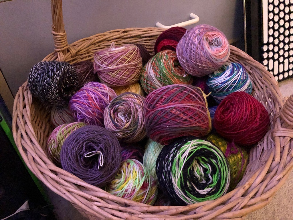 A basket full of brightly-coloured balls of leftover sock yarn.