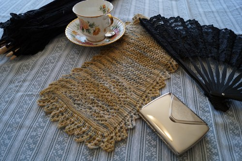 A Victorian Shetland lace scarf, nestled amongst a parasol, teacup, fan and silver cigarette case. Or maybe that case is for calling cards?