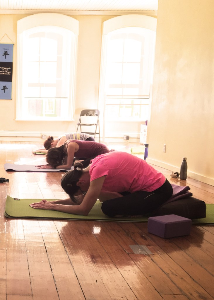 image of yoga students doing child pose in a sunny room