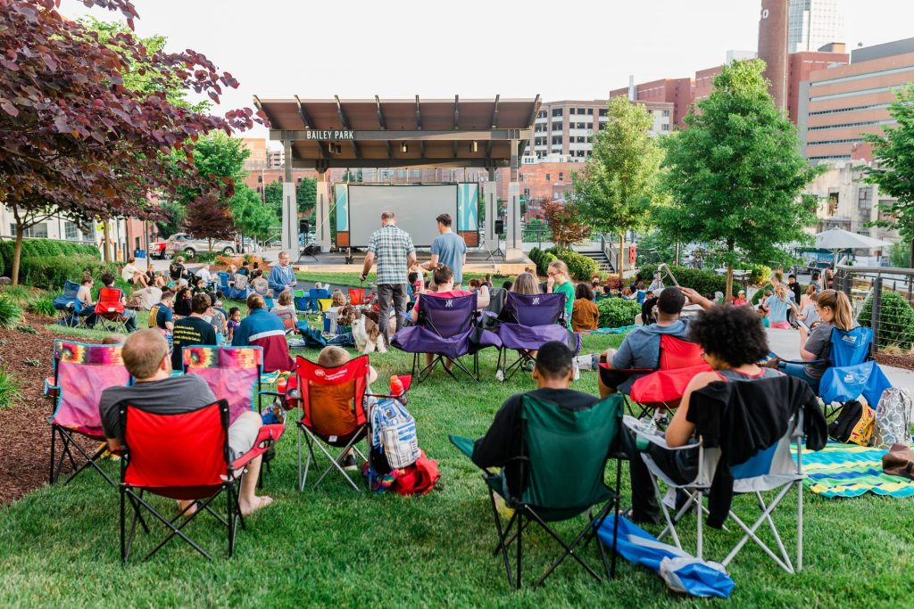 People sit on lawn at Bailey Park during Innovation & Cinema community event.