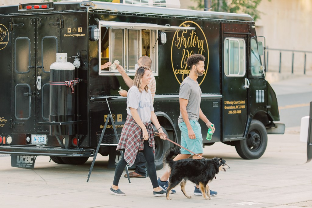 People walk in front of food truck with dog at Innovation & Cinema community event.