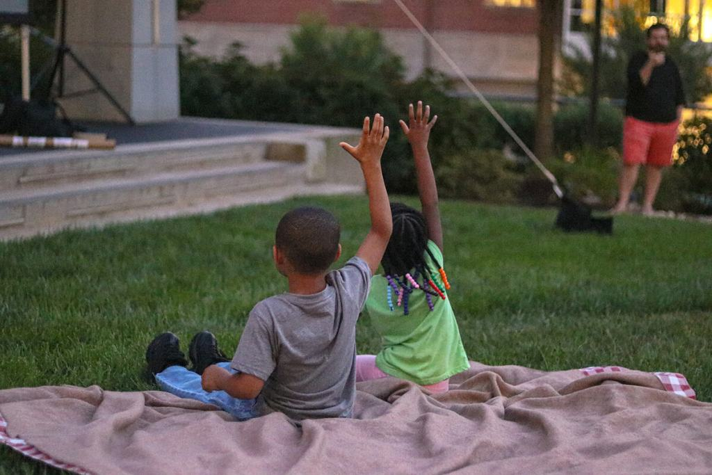 Children sit on lawn during Innovation & Cinema community event.