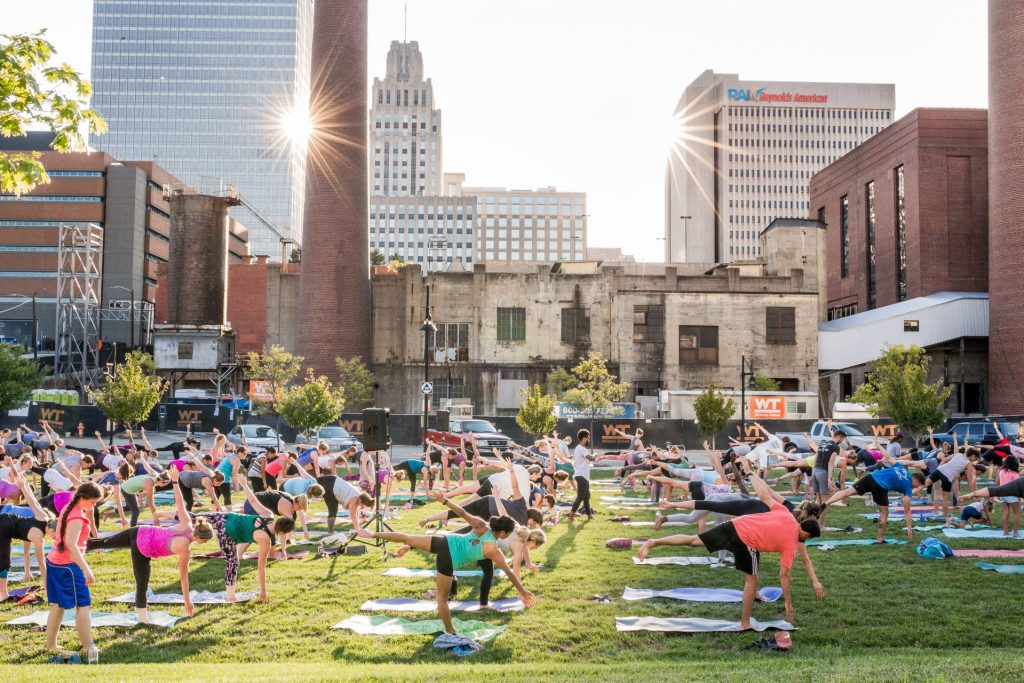 People practice yoga at Bailey Park during Sunset Salutations event.