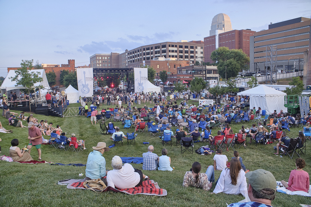 Lawn at Bailey Park with crowd sitting on lawn listening to music. Wnston-Salem skyline in background.