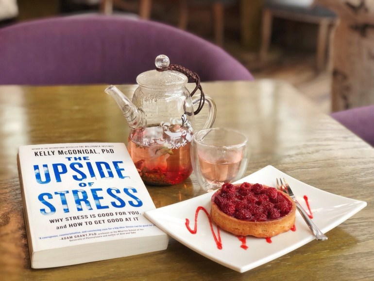 The Upside of Stress book on a table beside tea and a raspberry tart