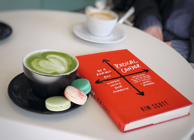 the book Radical Candor on a table beside a matcha latte and three macarons