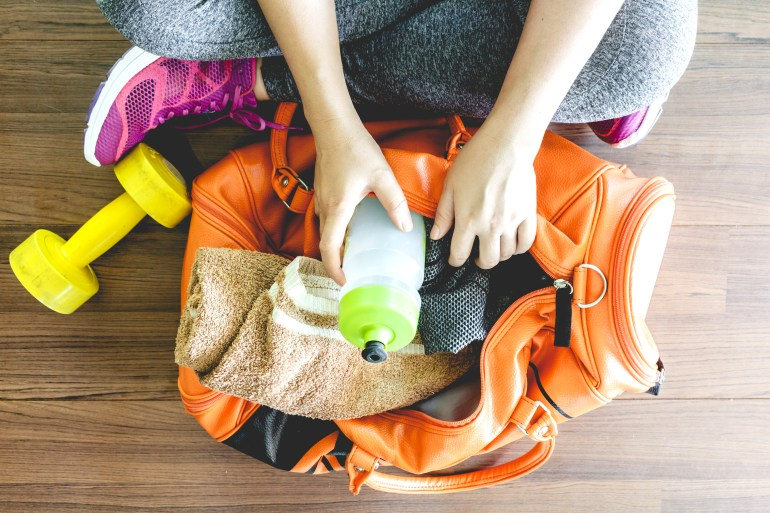 person sitting on the floor beside an exercise weight and gym bag with a towel and water bottle inside