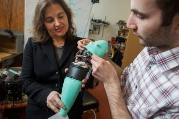 Andrew Marchese, doctoral candidate in EECS at MIT (right), and Dr. Daniela Rus, professor in EECS and Director of CSAIL, hold a soft robotic fish developed by the Distributed Robotics Laboratory. PHOTO: M. SCOTT BRAUER