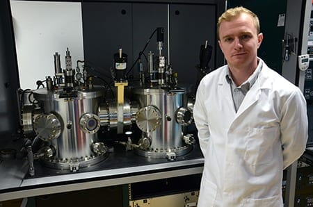 Dr Jon Major by the Stephenson Institute's sputtering deposition system – the first step in transforming ordinary window glass into solar panels.