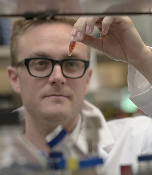 PHOTO BY JD HOWELL Chemical biology graduate student Andrew King, from McMaster University, examines a chemical used in drug discovery research