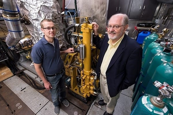 Sage Kokjohn, left, and Rolf Reitz check a room with test monitors and air regulators that are connected to an operating, one-cylinder diesel engine in the Caterpillar Engine Lab at the Engineering Research Building. Photo: Jeff Miller