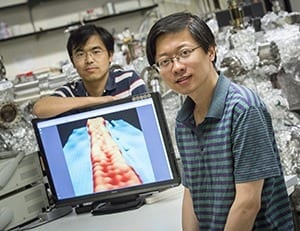 "Yaoyi Li (foreground) and Mingxing Chen, UWM physics postdoctoral researchers, display an image of a ribbon of graphene 1 nanometer wide. In the image, achieved with a scanning-tunneling microscope, atoms are visible as ""bumps."""